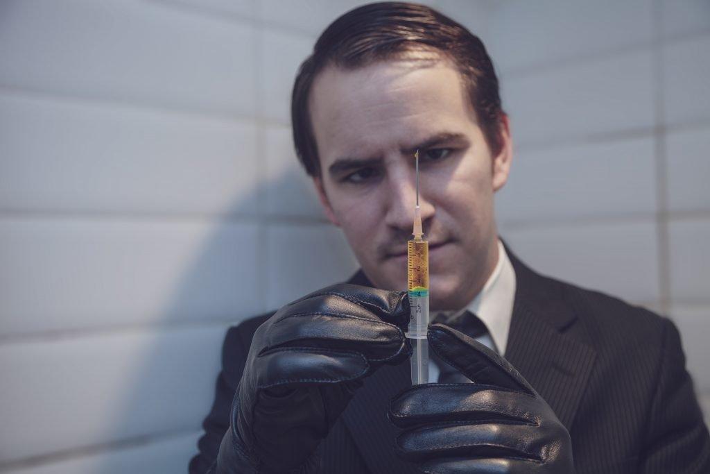 man holding syringe for knee injection